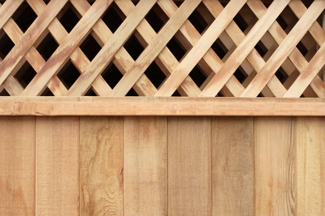 A light brown pine wooden fence with lattice on the top for added decoration.