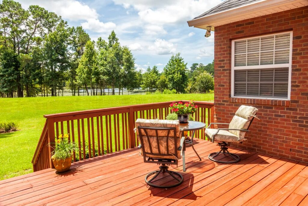 Image of a deck attached to a brick house with patio furniture next to a lawn and pond.