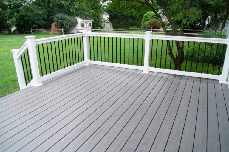 This image is of a gray deck with white railing next to a backyard lawn for a home.
